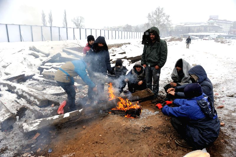 BELGRADE, Jan. 11, 2017 - A group of migrants sit by fire to warm themselves outside a shelter at an abandoned warehouse in freezing weather in Belgrade, Serbia, on Jan. 11, 2017. Low temperatures ...