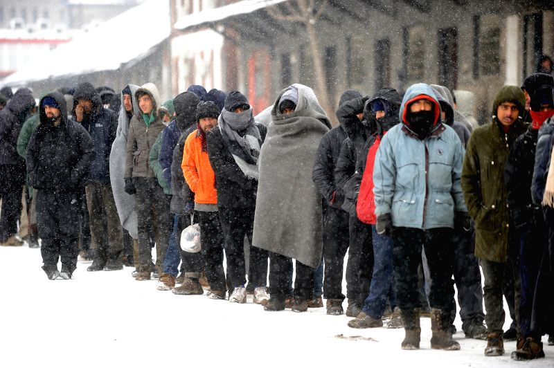 BELGRADE, Jan. 11, 2017 - Refugees and migrants stand in line for food distribution outside an improvised shelter at an abandoned warehouse in freezing weather in Belgrade, Serbia, on Jan. 11, 2017. ...