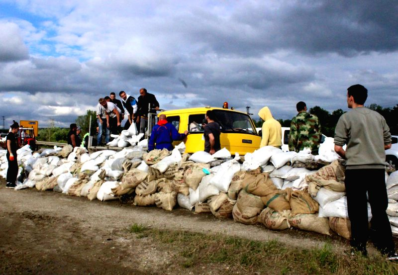 People build embankments by filling sacks with sand and building them into a wall to guard against flood in Umka of Belgrade, Serbia, on May 17, 2014. In short ...