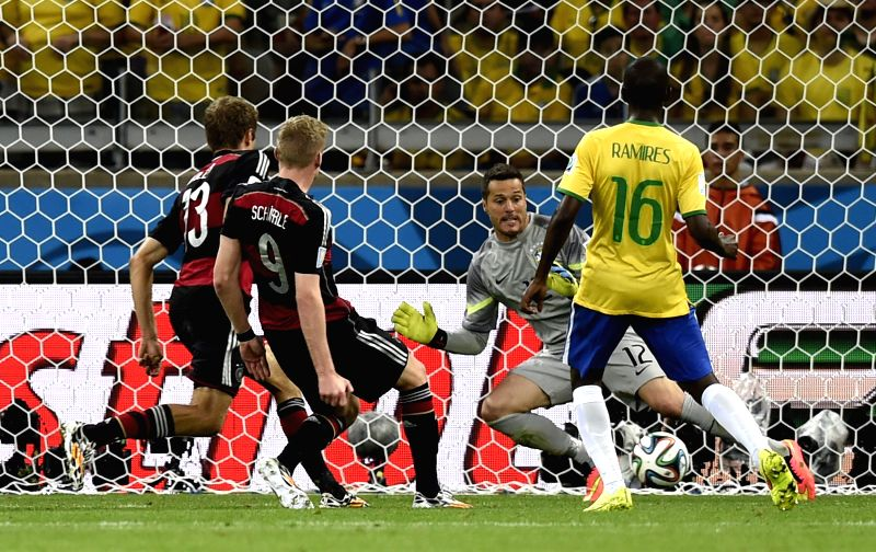 Brazil's goalkeeper Julio Cesar (2nd R) defends against Germany's Thomas Muller (1st L) and Andre Schuerrle (2nd L) during a semifinal match between Brazil ...
