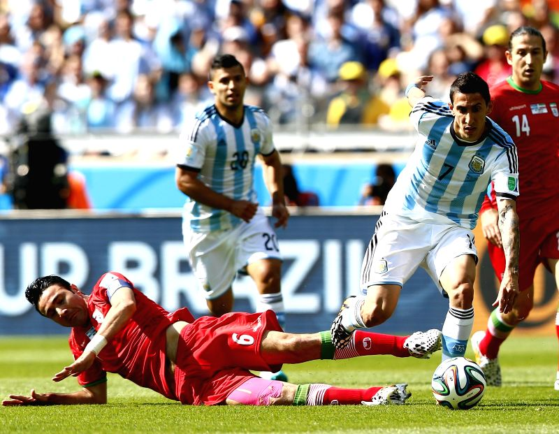 Angel Di Maria (R) of Argentina is tackled by Javad Nekounam of Iran during a Group F match between Argentina and Iran of 2014 FIFA World Cup at the Estadio .