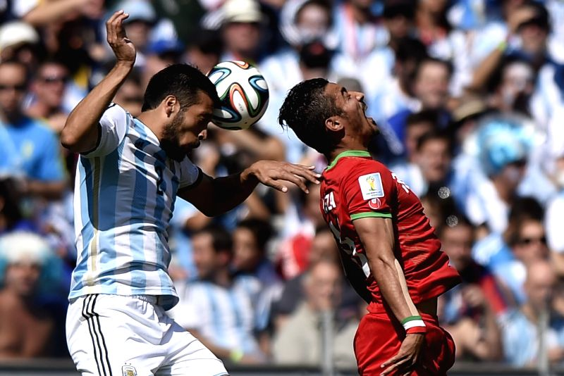 Ezequiel Garay (L) of Argentina vies with Reza Ghoochannejad of Iran during a Group F match between Argentina and Iran of 2014 FIFA World Cup at the Estadio .