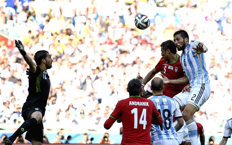 Ezequiel Garay (1st R) of Argentina vies with Amir-Hossein Sadeghi (2nd R) of Iran during a Group F match between Argentina and Iran of 2014 FIFA World Cup ..