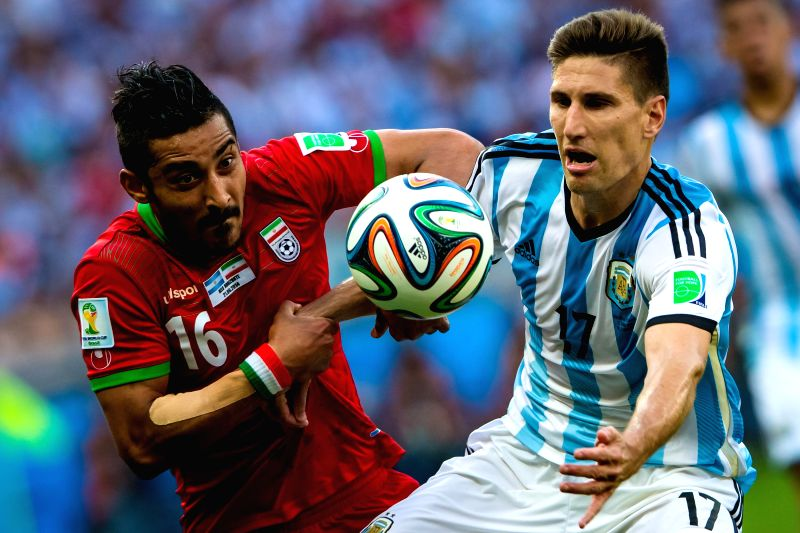 Federico Fernandez (R) of Argentina vies with Reza Ghoochannejad of Iran during a Group F match between Argentina and Iran of 2014 FIFA World Cup at the ...
