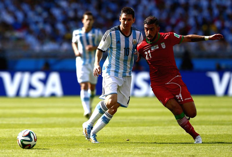 Lionel Messi (L) of Argentina vies with Ashkan Dejagah of Iran during a Group F match between Argentina and Iran of 2014 FIFA World Cup at the Estadio ...