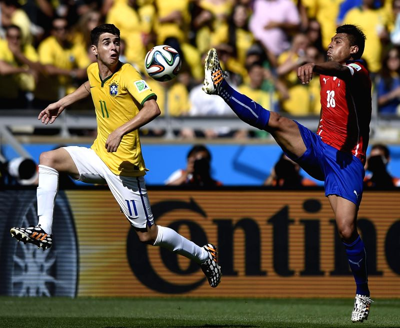 Brazil's Oscar (L) vies with Chile's Gonzalo Jara during a Round of 16 match between Brazil and Chile of 2014 FIFA World Cup at the Estadio Mineirao Stadium .