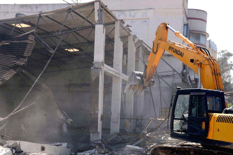 A BBMP bulldozer demolishes illegal structures near Arekere Lake in Bengaluru, on Dec 3, 2014.
