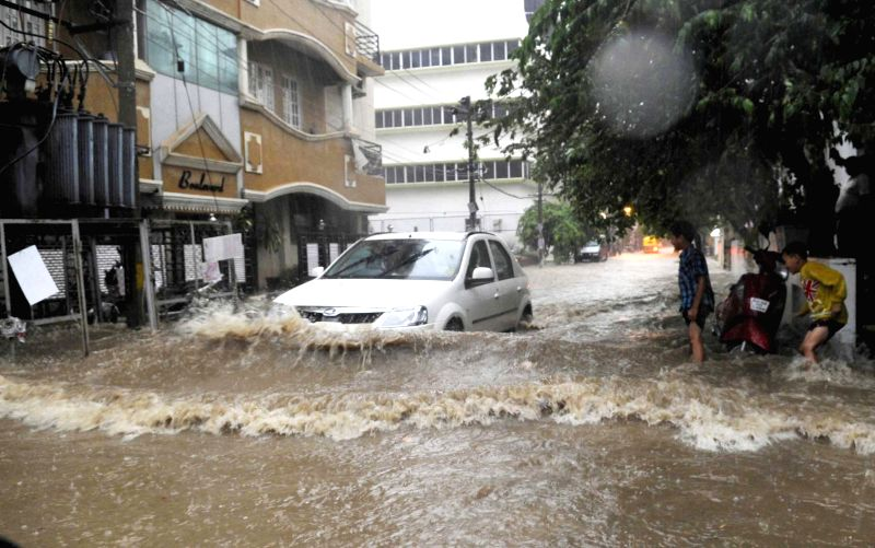 A car struggles  through waterlogged streets of Bengaluru during rains on April 25, 2015.