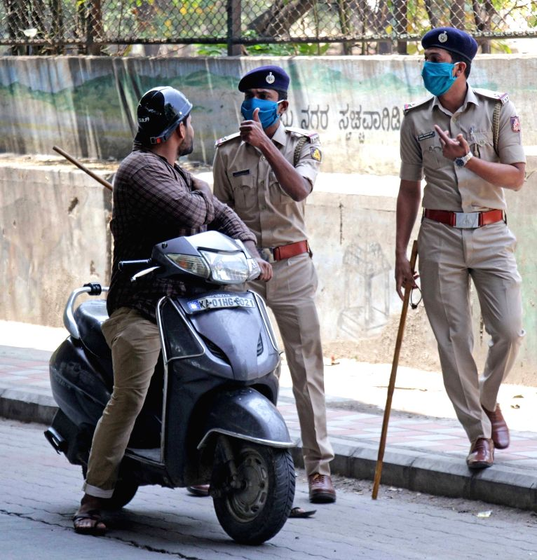 Bengaluru: A commuter being intercepted during complete lockdown imposed in 560 districts in 32 states and union territories across the country as precautionary measures to contain the spread of the coronavirus, in Bengaluru on March 24, 2020. (Photo