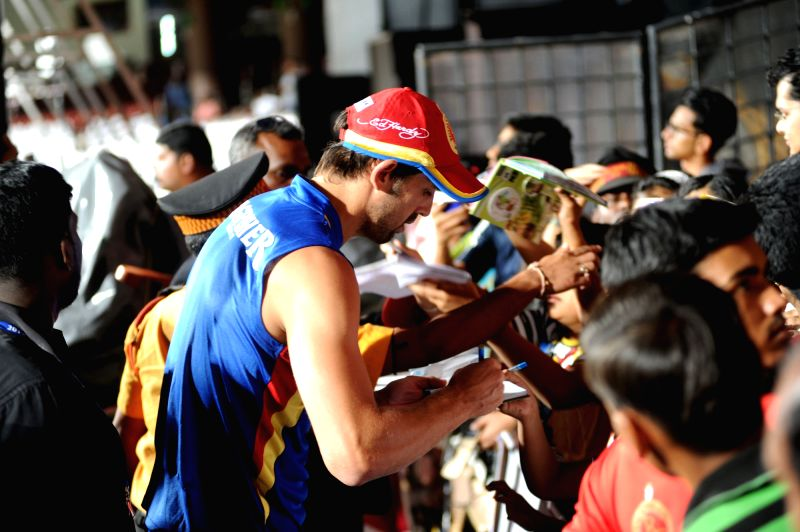 A Royal Challengers Bangalore player gives autographs to fans during a practice session at M Chinnaswamy Stadium in Bengaluru on April 21, 2015.