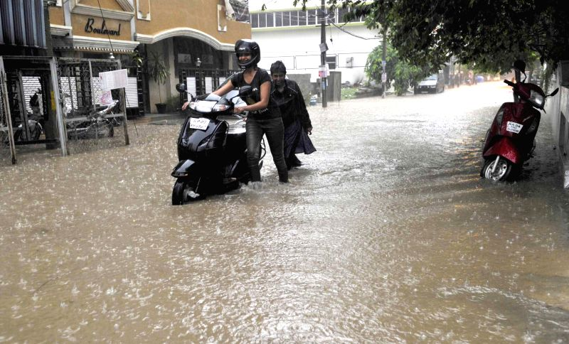 A woman wades through waterlogged streets of Bengaluru during rains on April 25, 2015.