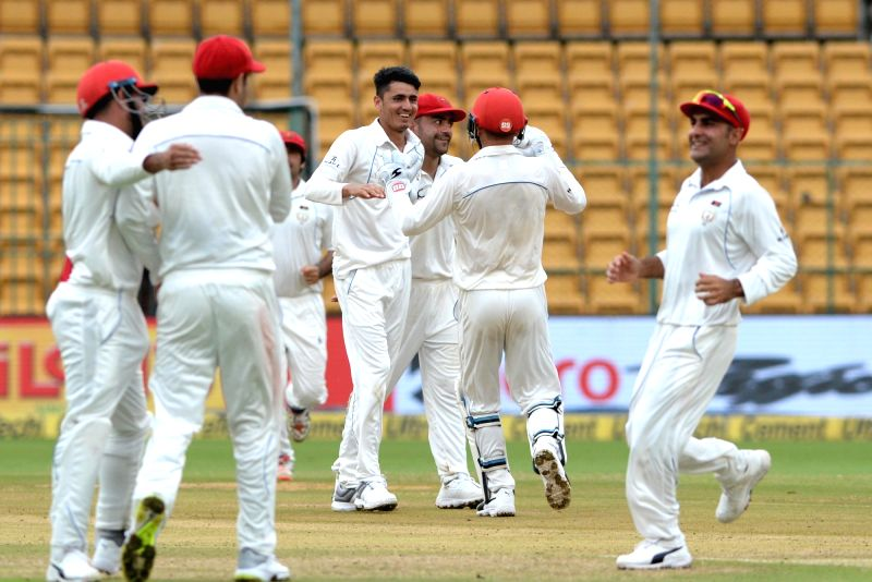 : Bengaluru: Afghanistan's players celebrate the fall of a wicket on Day 1 of the one-off test match between India and Afghanistan at M. Chinnaswamy Stadium, in Bengaluru on June 14, 2018. ...