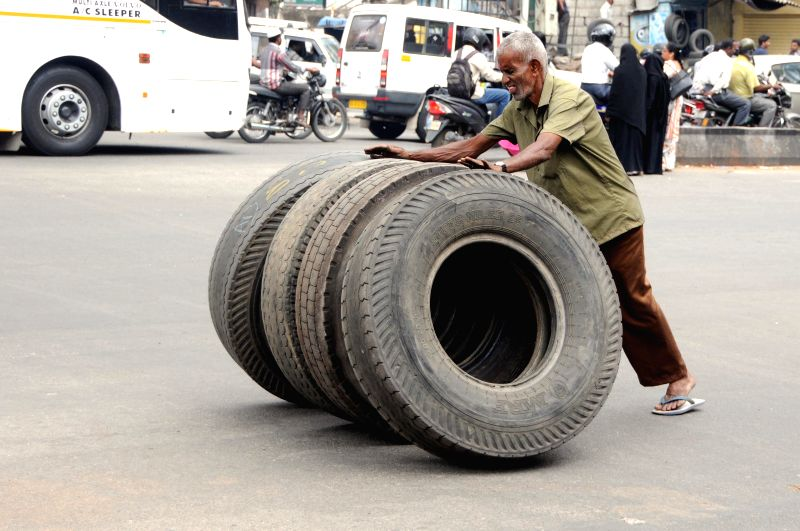 An labour pushes truck tyres in Bengaluru on May 1, 2015. 1st May is celebrates as May Day throughout the world.