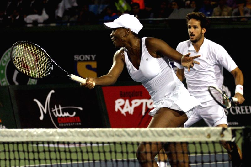 Bangalore Raptors` Venus Williams and Feliciano Lopez in action during their mixed doubles match of Champions Tennis League against Pune Marathas` Agnieszka Radwanska and Marcos Baghdatis .