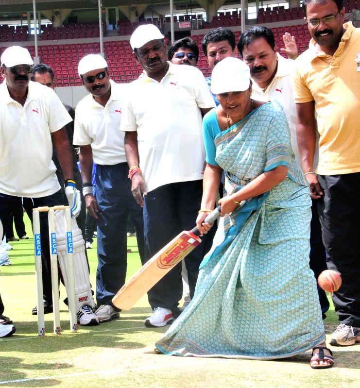 Bengaluru Mayor Shanta Kumari tries her hands at batting during the inauguration of Mayor's Cup cricket match at M Chinnaswamy Stadium in Bengaluru, on March 14, 2015.