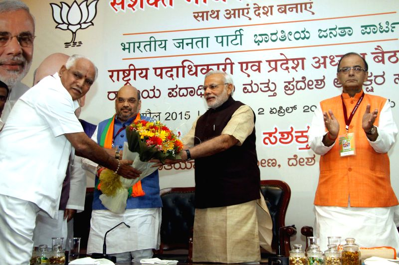 BJP leader B. S. Yeddyurappa greets Prime Minister Narendra Modi during BJP National Executive Committee meeting in Bengaluru on April 2, 2015. Also seen BJP chief Amit Shah and Union ... - Narendra Modi, Amit Shah and Arun Jaitley