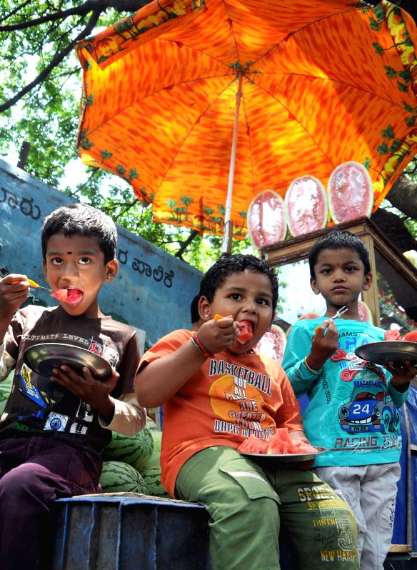 Children enjoy watermelon on a hot day in Bengaluru, on April 10, 2015.