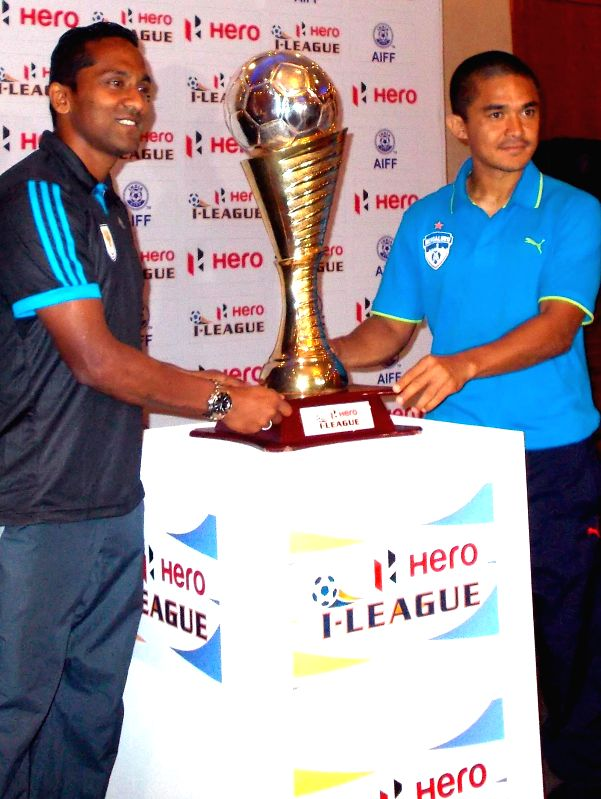 Dempo SC captain Clifford Miranda and Bengaluru FC captain Sunil Chhetri with the Hero - I - League trophy during a press conference in Bengaluru, on Jan 16, 2015. - Clifford Miranda