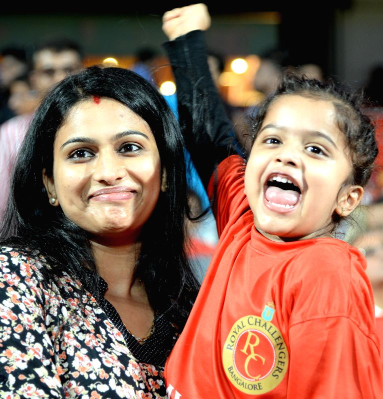 Fans cheer during an IPL-2015 match between Royal Challengers Bangalore and Mumbai Indians at M Chinnaswamy Stadium, in Bengaluru, on April 19, 2015.