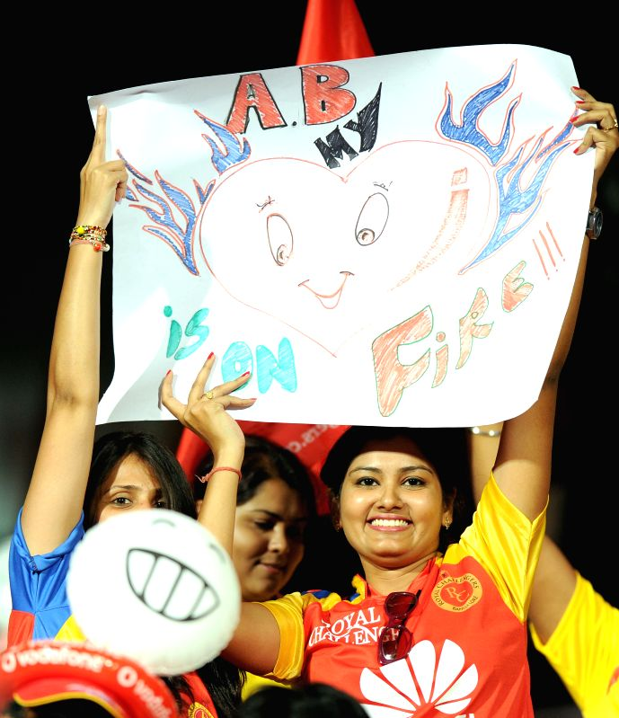 Fans cheer during an IPL-2015 match between Royal Challengers Bangalore and Chennai Super Kings at M Chinnaswamy Stadium, in Bengaluru, on April 22, 2015.