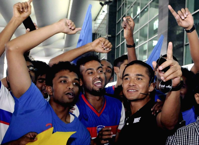 Bengaluru Football Club players celebrate their win against Dempo Sports Club of Goa during the I League on their arrival at Kempegowda International Airport in Bangalore on April 22, 2014.