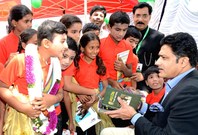 Former Indian cricketer Anil Kumble with children at the launch of `Books my friend` in Bengaluru, on Dec 10, 2014.