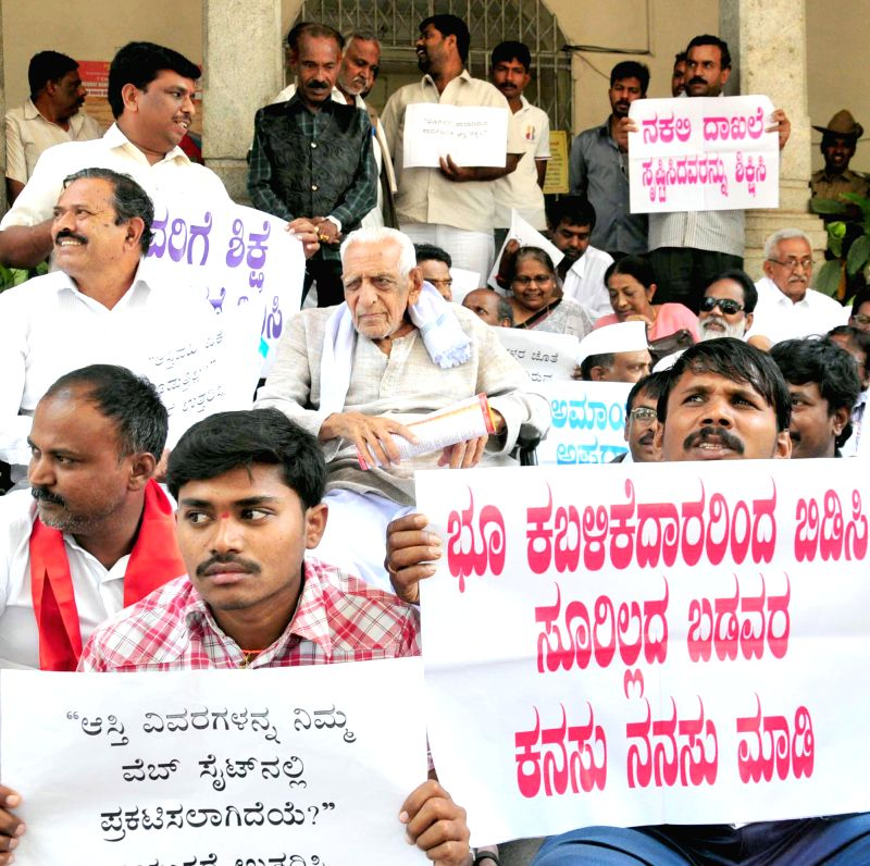Freedom fighter H S Doreswamy and his supporters stage a protest in front of BBMP office against illegal land occupations in Bengaluru on March 10, 2015.