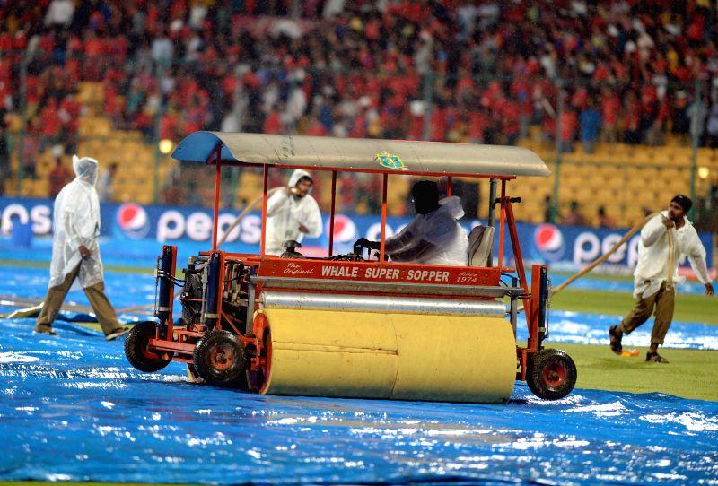 Ground staff at work as rain disrupts the IPL-2015 match between Royal Challengers Bangalore and Rajasthan Royals at M Chinnaswamy Stadium in Bangaluru on April 29, 2015.
