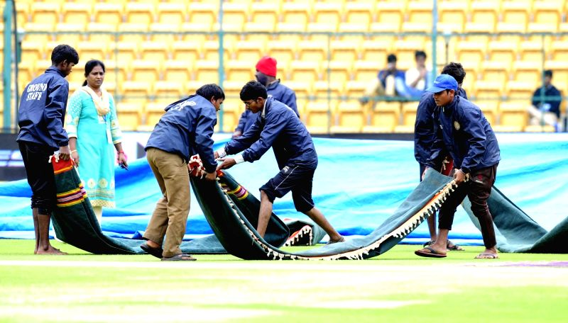 Bengaluru: Groundsmen cover the pitch with tarpaulin sheets as rain delay the start of the 4th day of the second test match between India and South Africa at M Chinnaswamy Stadium in ...