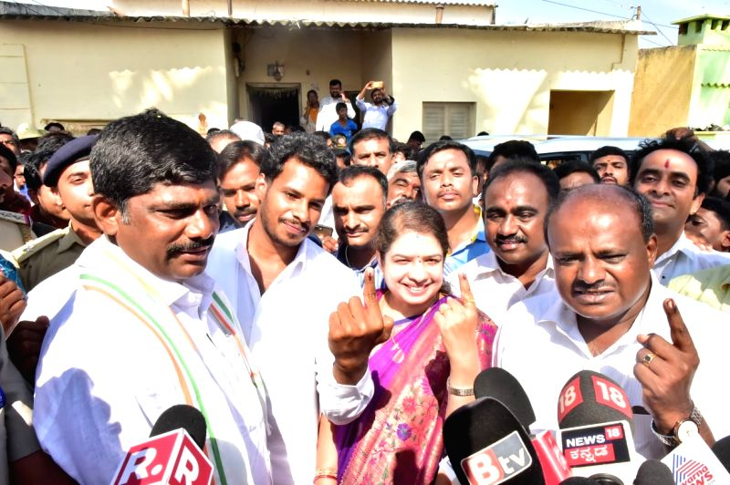 Karnataka Chief Minister HD Kumaraswamy with his wife Anitha Kumaraswamy, son Nikhil Gowda show their forefinger marked with indelible ink after casting vote during the second phase of Lok Sabha polls