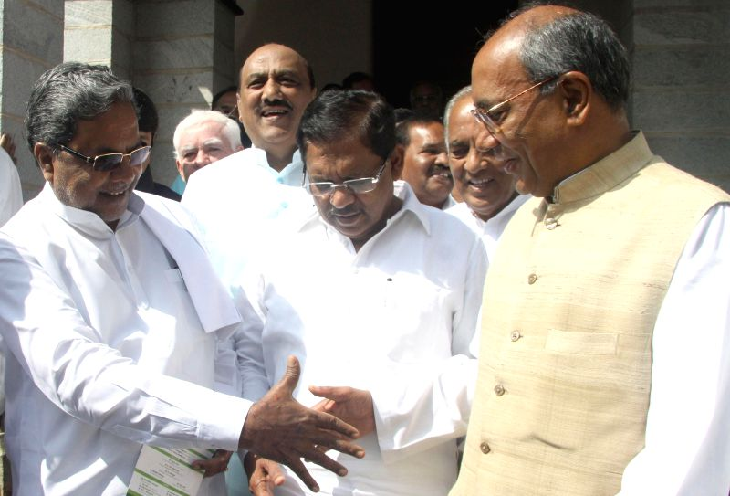 Karnataka Chief Minister K Siddaramaiah and MLC G Parmeshwar greeting AICC General Secretary Digvijaya Singh in Bengaluru on Jan. 24, 2015. - Secretary Digvijaya Singh
