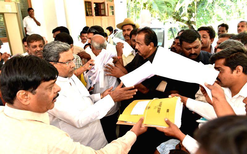 Karnataka Chief Minister Siddaramaiah interacts with public during his Janata Darshan, in Bengaluru on Nov 18, 2014. - Siddaramaiah