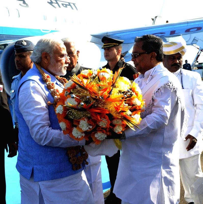 Karnataka Chief Minister Siddaramaiah receives Prime Minister Narendra Modi on his arrival at Yelahanka Air-force Station, in Bengaluru on Feb 18, 2015. - Siddaramaiah and Narendra Modi