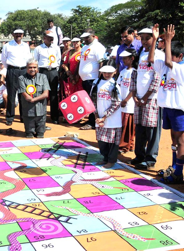 ​Karnataka Commissioner for Persons with Disabilities K ​ ​ S Rajanna plays ​ a game of​  snakes and ladders ​​  with children during ​ `CBM Include Vidya Abhiyan - 2014` ..