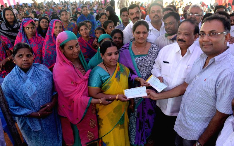 Karnataka Food and Civil Supply Minister Dinesh Gundu Rao and Karnataka Information Minister R Roshan Baig distribute cheques during a programme at Gandhi Nagar, in Bengaluru on Dec 23, ... - Dinesh Gundu Rao and R Roshan Baig
