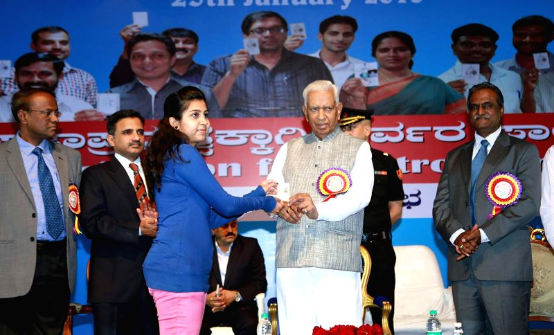 Karnataka Governor Vajubhai Rudabhai Vala hands over a voter's identity card to a girl during a programme organised on National Voters' Day in Bengaluru, on Jan 25, 2015.