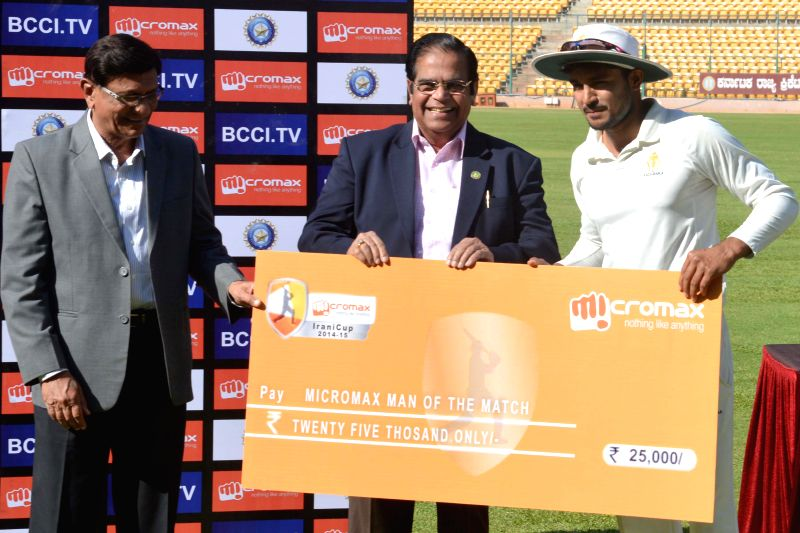 Karnataka player Manish Pandey receives Man of the Series cheque during the presentation ceremony of Irani Cup at M Chinnaswamy Stadium, in Bengaluru on March 20, 2015. - Manish Pandey