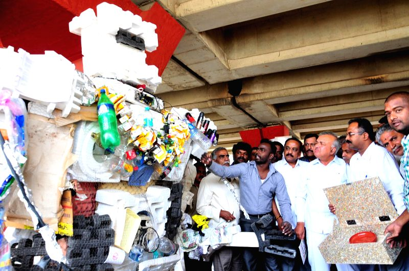 Karnataka Transport Minister Ramalinga Reddy looks at the replica of robot made from Garbage (used bottle, thermocal, juice packet etc.) during `Kasa Market` (best price and better place .. - Ramalinga Reddy