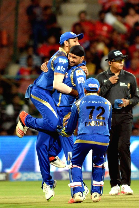 Mumbai Indians celebrate fall of a wicket during an IPL-2015 match between Royal Challengers Bangalore and Mumbai Indians at M Chinnaswamy Stadium, in Bengaluru, on April 19, 2015.