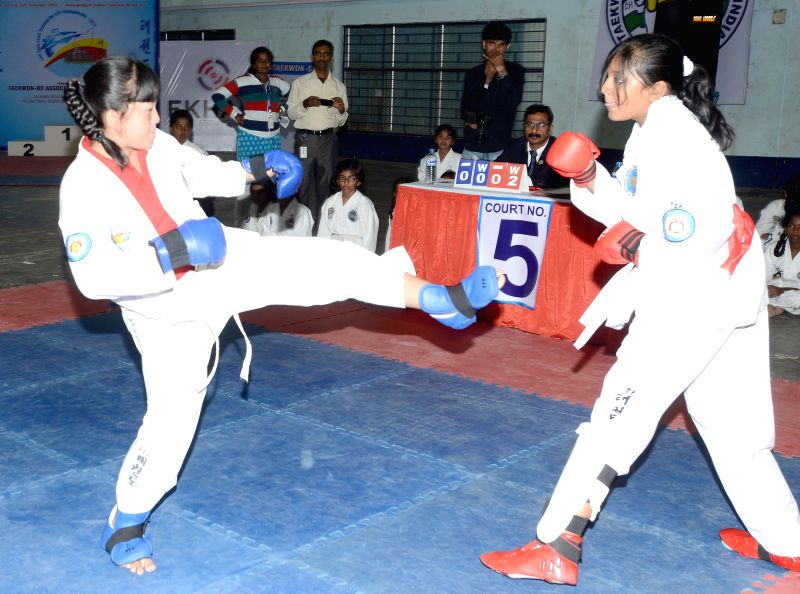 Participants in action during the 14th State Level Taekwondo Championship - 2014 at Koramangala Indoor Stadium in Bengaluru, on Nov 24, 2014.