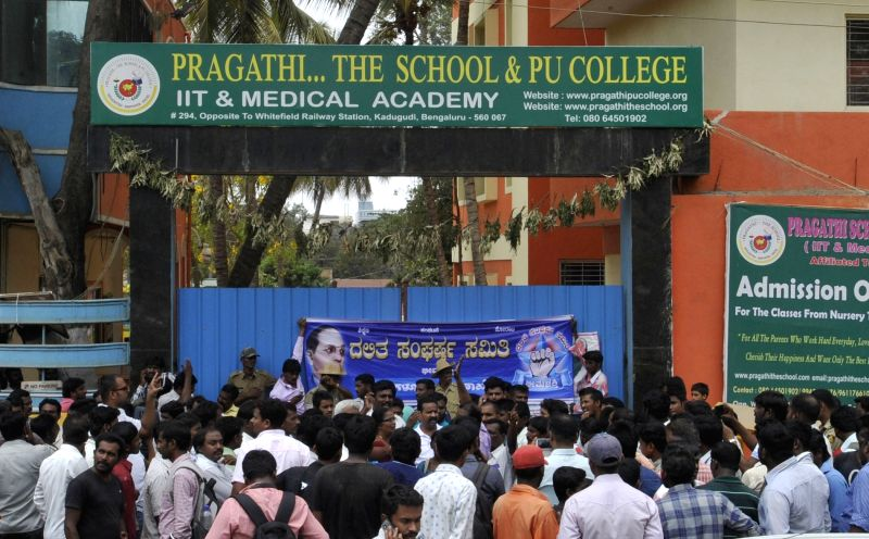 People in large numbers gather outside the Bengaluru school where an 18-year-old girl student was shot dead in her school premises by an office attendant for spurning his advances in ...