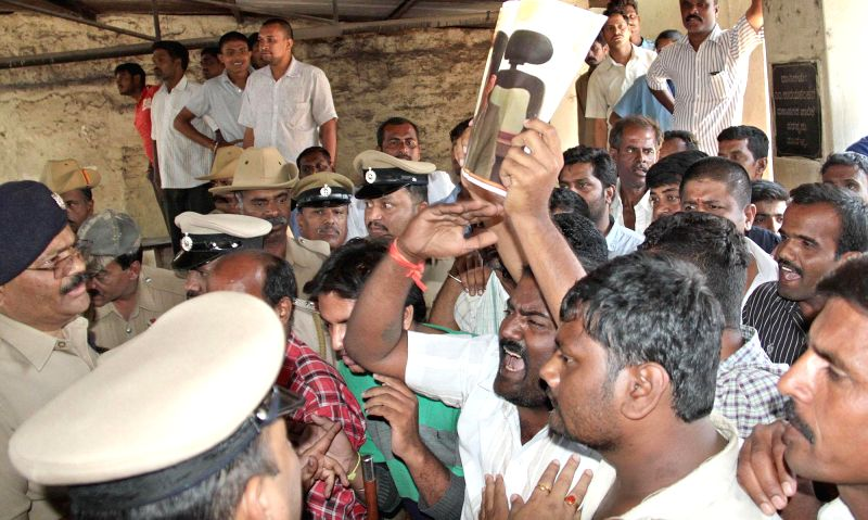 People protest against Karnataka Chief Minister as he visits the Victoria Hospital to pay his last respect to Bangalore Additional Commissioner of Commercial Taxes D K Ravi, who was found ...