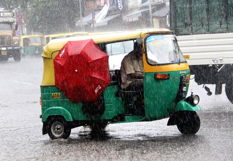 People use umbrellas to protect themselves from heavy rains in Bengaluru on May 16, 2015.