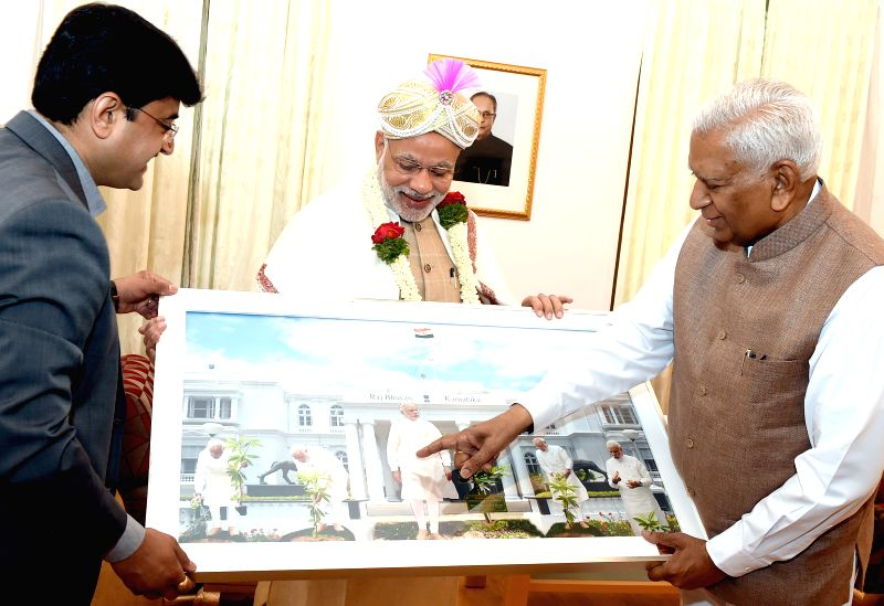 Prime Minister Narrendra Modi being felicitated by Karnataka Governor Vajubhai Rudabhai Vala at Raj Bhavan, in Bengaluru, on April 4, 2015. - Narrendra Modi