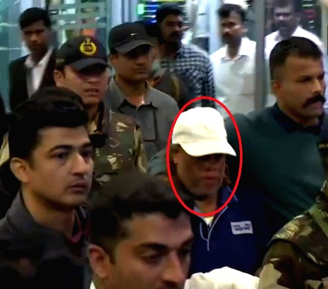 Bengaluru: Ravi Pujari (wearing white cap), accused of committing serious offences including murder and extortion, reaches Kempegowda International Airport.