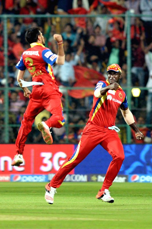 Royal Challengers Bangalore players Darren Sammy and Yuzvendra Chahal celebrate fall of a wicket during an IPL-2015 match between Royal Challengers Bangalore and Sunrisers Hyderabad at M ...