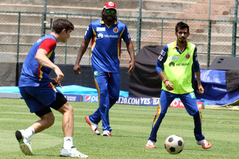 Royal Challengers Bangalore players Yuzvendra Chahal and Chris Gayle during a practice session at M Chinnaswamy Stadium, in Bengaluru, on May 1, 2015.