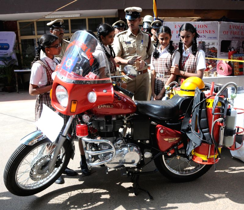 School students look at fire fighting motor bike during a programme organised on National Consumers Day,in Bengaluru on Dec 24, 2014.