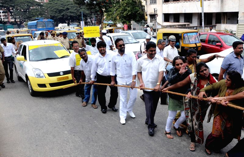 Taxi drivers and operators pull a taxi with a rope to protest against private taxi agencies for reducing taxi fares in Bengaluru on Dec 11, 2014.