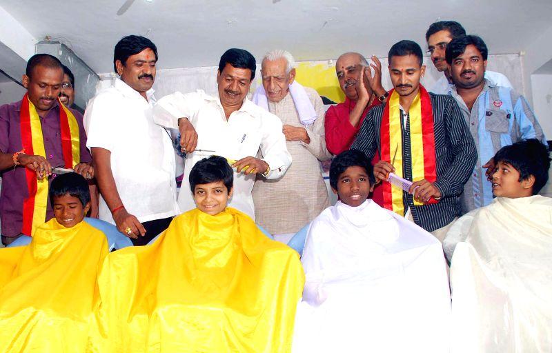 The members of Karnataka State Savita Samaj give children a haircut as they celebrate the 65th birthday of actor Rajinikanth in Bengaluru, on Dec 12, 2014.